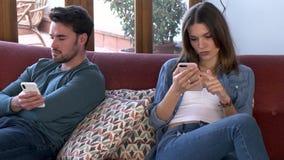 Νέο ζεύγος που αγνοεί το ένα το άλλο που χρησιμοποιεί το τηλέφωνο μετά από ένα επιχείρημα καθμένος στον καναπέ στο σπίτι φιλμ μικρού μήκους