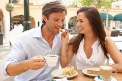 Νέο ζεύγος που απολαμβάνει τον καφέ και το κέικ σε Caf� Στοκ Φωτογραφία
