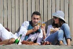 Νέο ζεύγος που απολαμβάνει picnic στην παραλία στοκ εικόνα με δικαίωμα ελεύθερης χρήσης