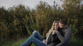 Νέο ζεύγος που απολαμβάνει το ένα το άλλο που κάθεται στο χορτοτάπητα στο πάρκο φθινοπώρου απόθεμα βίντεο