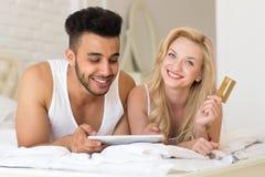 Νέο ζεύγος που βρίσκεται στο κρεβάτι που χρησιμοποιεί τη σε απευθείας σύνδεση πληρωμή αγορών πιστωτικών καρτών λαβής υπολογιστών  Στοκ Εικόνες