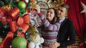 Νέο ζεύγος που διακοσμεί ένα χριστουγεννιάτικο δέντρο στο σπίτι απόθεμα βίντεο