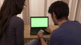 Νέο ζεύγος που δοκιμάζει τα ζητήματα με την πιστωτική κάρτα κάνοντας on-line να ψωνίσει χρησιμοποιώντας ένα lap-top με την πράσιν απόθεμα βίντεο