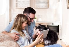 Νέο ζεύγος που εξετάζει την ταμπλέτα στο σπίτι στοκ φωτογραφία