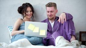 Νέο ζεύγος που εξετάζει το όργανο ελέγχου lap-top, τύποι που κάθεται στις πυτζάμες στο κρεβάτι απόθεμα βίντεο