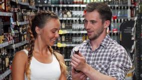 Νέο ζεύγος που επιλέγει το κρασί που αγοράζει στην υπεραγορά απόθεμα βίντεο