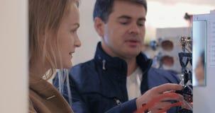 Νέο ζεύγος που επιλέγει τα γυαλιά ηλίου στο κατάστημα απόθεμα βίντεο