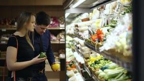Νέο ζεύγος που επιλέγει τα φρέσκα λαχανικά μέσα απόθεμα βίντεο