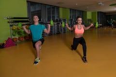 Νέο ζεύγος που κάνει τη βαρέων βαρών άσκηση για τα πόδια Στοκ φωτογραφίες με δικαίωμα ελεύθερης χρήσης