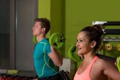 Νέο ζεύγος που κάνει τη βαρέων βαρών άσκηση για τα πόδια Στοκ Φωτογραφία