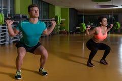 Νέο ζεύγος που κάνει τη βαρέων βαρών άσκηση για τα πόδια Στοκ Εικόνες