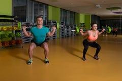 Νέο ζεύγος που κάνει τη βαρέων βαρών άσκηση για τα πόδια Στοκ φωτογραφία με δικαίωμα ελεύθερης χρήσης