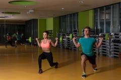 Νέο ζεύγος που κάνει τη στάση οκλαδόν Barbell άσκησης Στοκ Φωτογραφίες