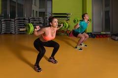 Νέο ζεύγος που κάνει τη στάση οκλαδόν Barbell άσκησης Στοκ Φωτογραφία