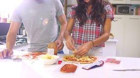 Νέο ζεύγος που κατασκευάζει την πίτσα στην κουζίνα από κοινού φιλμ μικρού μήκους