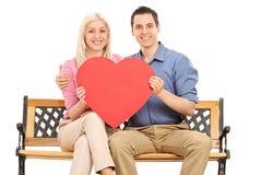 Νέο ζεύγος που κρατά μια κόκκινη καρδιά καθισμένη σε έναν πάγκο Στοκ Φωτογραφίες