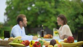 Νέο ζεύγος που μιλά ενώ έχοντας το μεσημεριανό γεύμα, φρούτα μη ΓΤΟ, ελεύθερα τρόφιμα φυτοφαρμάκων απόθεμα βίντεο