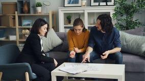 Νέο ζεύγος που μιλά με το realtor που εξετάζει τα έγγραφα στο εσωτερικό στο καινούργιο σπίτι φιλμ μικρού μήκους