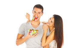 Ευτυχές ζεύγος που τρώει τη σαλάτα μαζί σε ένα άσπρο υπόβαθρο Στοκ Εικόνα
