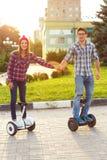 Νέο ζεύγος που οδηγά hoverboard - ηλεκτρικό μηχανικό δίκυκλο, προσωπική ΕΚ Στοκ φωτογραφίες με δικαίωμα ελεύθερης χρήσης