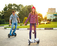 Νέο ζεύγος που οδηγά hoverboard - ηλεκτρικό μηχανικό δίκυκλο, προσωπική ΕΚ Στοκ Εικόνες