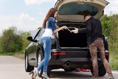 Νέο ζεύγος που παίρνει έτοιμο να αλλάξει ένα ελαστικό αυτοκινήτου στοκ εικόνες
