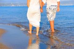 Νέο ζεύγος που περπατά κατά μήκος της μόνης παραλίας στο ηλιοβασίλεμα στοκ φωτογραφίες