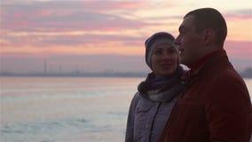 Νέο ζεύγος που περπατά στην παραλία στο βράδυ το χειμώνα απόθεμα βίντεο
