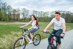 Νέο ζεύγος που πηγαίνει σε ένα ποδήλατο μια ηλιόλουστη ημέρα σε ένα πάρκο πόλεων Στοκ φωτογραφίες με δικαίωμα ελεύθερης χρήσης