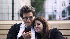 Νέο ζεύγος που προσέχει ένα βίντεο σε ένα smartphone έξω φιλμ μικρού μήκους