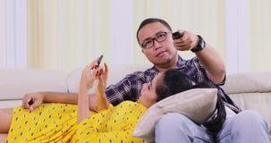 νέο ζεύγος που προσέχει τη TV στο καθιστικό απόθεμα βίντεο