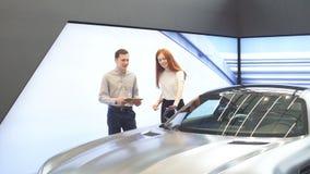 Νέο ζεύγος που στέκεται στη εμπορία αυτοκινήτων και που λαμβάνει την απόφασή τους απόθεμα βίντεο