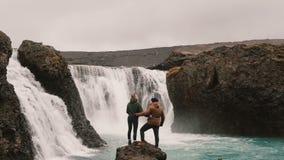 Νέο ζεύγος που στην Ισλανδία Διακινούμενοι άνδρας και γυναίκα που στέκονται κοντά στον ισχυρό καταρράκτη και την αύξηση των χεριώ φιλμ μικρού μήκους