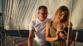 Νέο ζεύγος που ταξιδεύει με το γιοτ και που χρησιμοποιεί το κινητό τηλέφωνο απόθεμα βίντεο