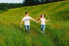 Νέο ζεύγος που τρέχει μαζί σε μια πράσινη περιοχή στοκ εικόνες