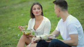 Νέο ζεύγος που τρώει τη συνεδρίαση σαλάτας στη χλόη, πικ-νίκ από κοινού απόθεμα βίντεο