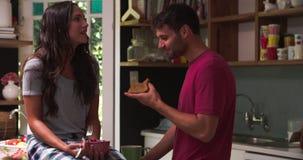 Νέο ζεύγος που τρώει το πρόγευμα στην κουζίνα από κοινού απόθεμα βίντεο