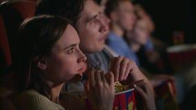 Νέο ζεύγος που τρώει popcorn από ένα κιβώτιο Fiends συνδέουν τον κινηματογράφο προσοχής απόθεμα βίντεο