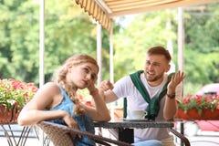 Νέο ζεύγος που υποστηρίζει καθμένος στον καφέ, υπαίθριο στοκ φωτογραφία με δικαίωμα ελεύθερης χρήσης