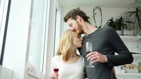 Νέο ζεύγος που φιλά και που πίνει το κόκκινο κρασί απόθεμα βίντεο
