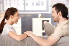 Νέο ζεύγος που χαμογελά ευτυχώς το ένα το άλλο στο σπίτι στοκ φωτογραφία με δικαίωμα ελεύθερης χρήσης