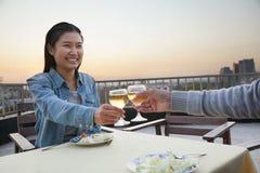 Νέο ζεύγος που χαμογελά και που τρώει στην κορυφή στεγών, ψήσιμο Στοκ Φωτογραφίες