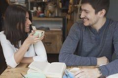 Νέο ζεύγος που χαμογελά στη καφετερία στοκ φωτογραφία