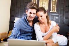 Νέο ζεύγος που χρησιμοποιεί έναν φορητό προσωπικό υπολογιστή σε ένα ασιατικό δωμάτιο ξενοδοχείου Στοκ Φωτογραφία