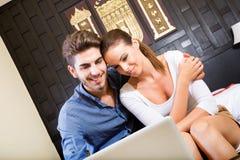 Νέο ζεύγος που χρησιμοποιεί έναν φορητό προσωπικό υπολογιστή σε ένα ασιατικό δωμάτιο ξενοδοχείου Στοκ Εικόνα