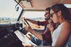 Νέο ζεύγος που χρησιμοποιεί έναν χάρτη σε ένα roadtrip για τις κατευθύνσεις στοκ φωτογραφία με δικαίωμα ελεύθερης χρήσης