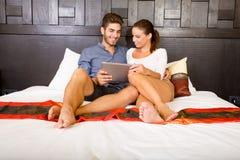 Νέο ζεύγος που χρησιμοποιεί ένα PC ταμπλετών σε ένα ασιατικό δωμάτιο ξενοδοχείου Στοκ Εικόνα