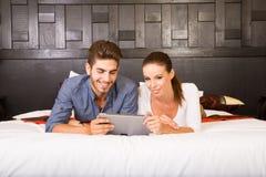 Νέο ζεύγος που χρησιμοποιεί ένα PC ταμπλετών σε ένα ασιατικό δωμάτιο ξενοδοχείου Στοκ φωτογραφίες με δικαίωμα ελεύθερης χρήσης