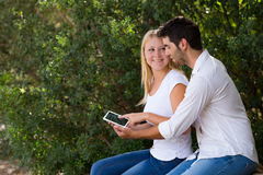 Νέο ζεύγος που χρησιμοποιεί Διαδίκτυο υπαίθριο με την ψηφιακή ταμπλέτα Στοκ Φωτογραφία