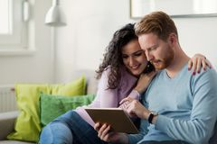 Νέο ζεύγος που χρησιμοποιεί την ψηφιακή ταμπλέτα στο σπίτι Στοκ φωτογραφία με δικαίωμα ελεύθερης χρήσης